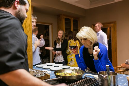KC documentary photographers photo of chef cooking dinner at birthday party while surprised lady looks on