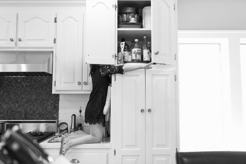 Kansas City day in the life family documentary session genuine fun storytelling moment girl getting snack in cabinet picture