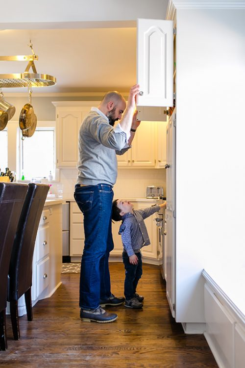 Kansas City day in the life session dad looking in cabinet with son for lunch sweet real photo