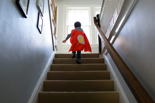 Kansas City family documentary photographer kid running up stairs with cape photo