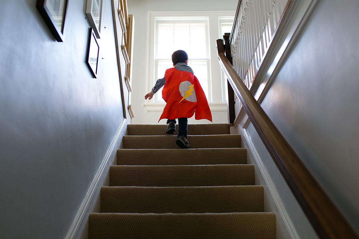 Kansas City family documentary photographer kid running up stairs with cape photo