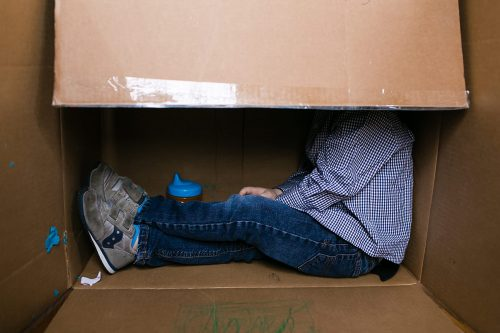 Kansas City family documentary storytellers fun real moment of boy in his box with sippy cup photo