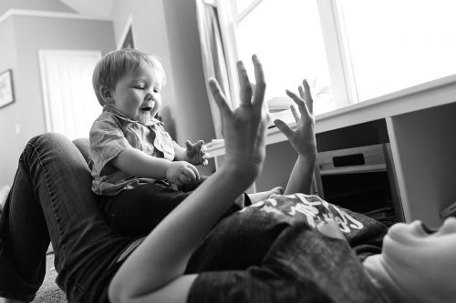 Kansas City husband wife documentary photographers funny laughing picture of boy playing with mom