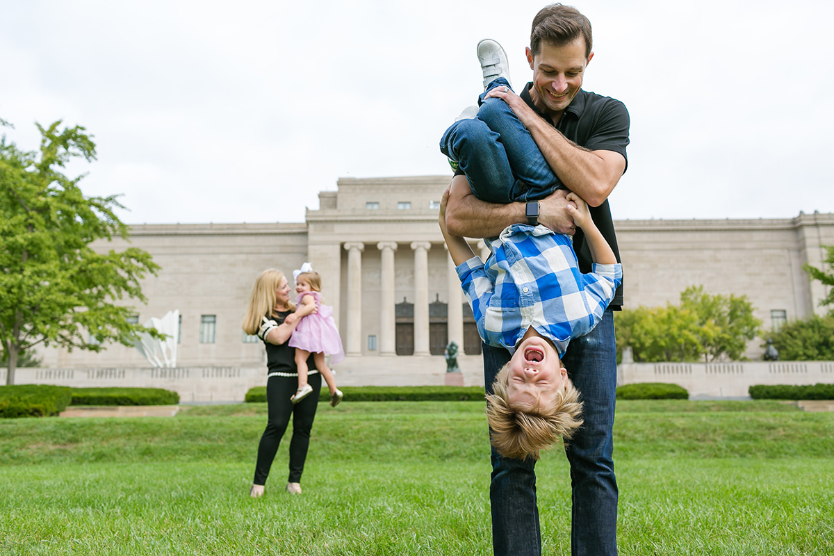 Kansas City photographer honest real life boy upside down crying genuine family photo session at Nelson Atkins