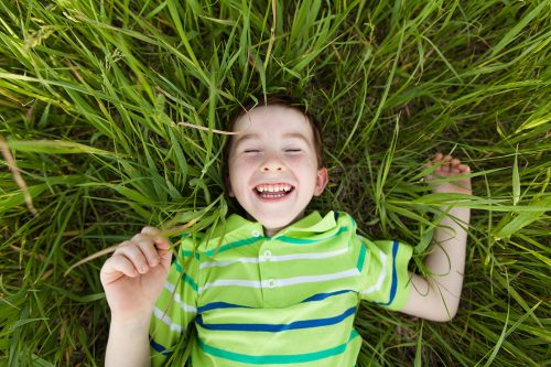 authentic happy joyful kid laying in grass genuine moment picture