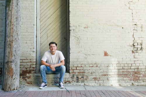 confident senior sitting in urban brick picture