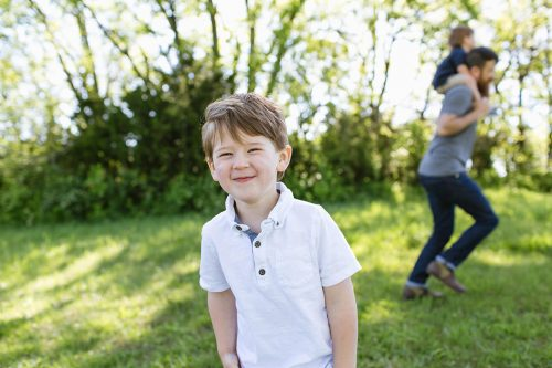 cute grinning boy with dad giving piggyback ride to boy in background relaxed family
