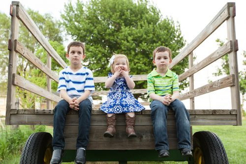 cute laughing girl and grumpy boys on wagon family portrait session