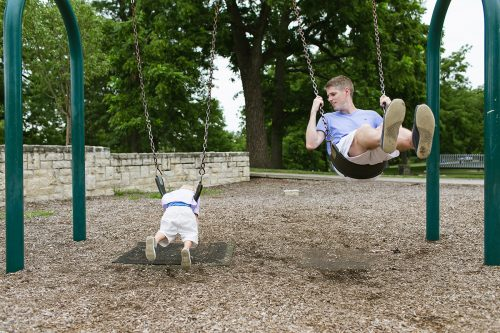 dad and son swinging on stomach at playground genuine moment