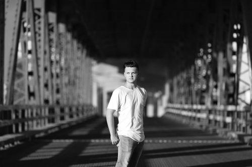 dramatic striking picture of senior boy on old metal bridge