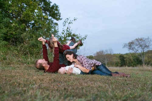 endearing photo of family playing in park