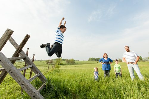 epic fun real moment kid jumping off fence family session picture