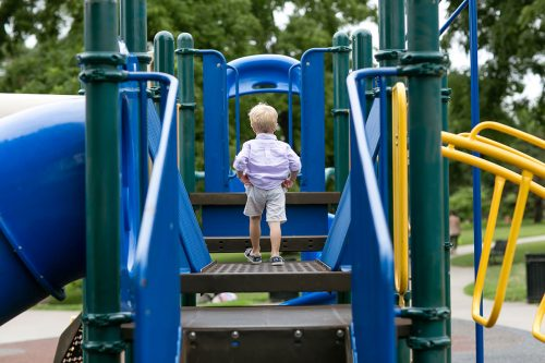 family at park boy pulling up pants on playground