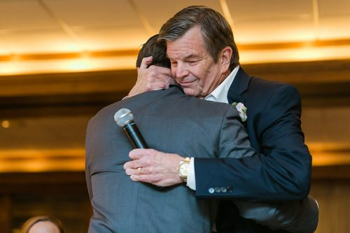 father hugging groom real moment photo