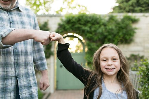 fun genuine moment girl fist bumping dad