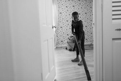 fun photo of kid vacuuming floor in spiderman outfit