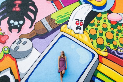 fun senior picture of girl by bright colorful mural wall laughing in Kansas City