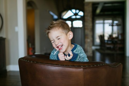 funny kid with sucker in mouth in-home real moment documentary photo