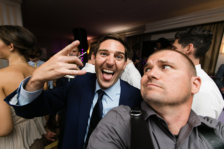 funny wedding photographer silly face selfie with guest