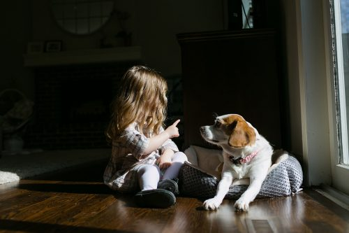 girl talking to dog with finger real life unposed photo