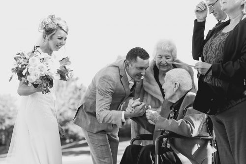 heartwarming candid photo of groom shaking grandpa hand