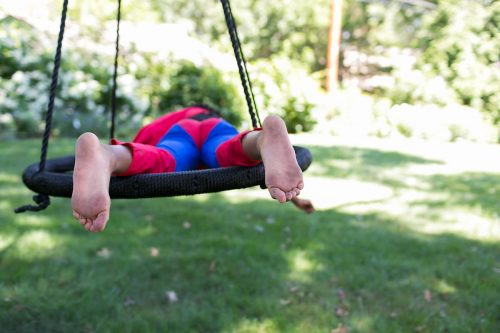 kid relaxing on swing in superman outfit real documentary photo