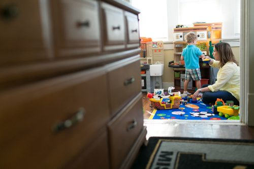 mom playing make believe cooking with son in real family documentary photo