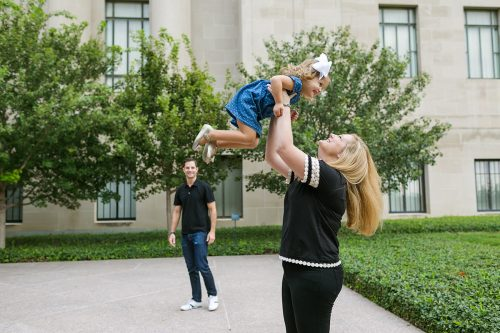 mom tossing daughter in air fun family photo session