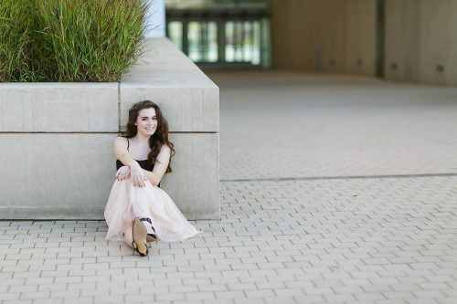 pretty senior picture in Kansas City girl sitting by wall
