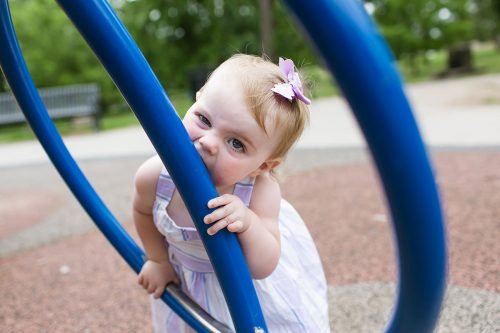 real candid fun moment of kid biting playground equipment with funny face photo