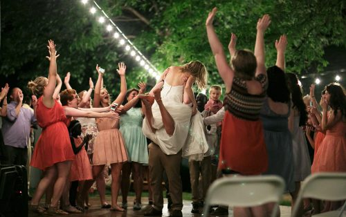 real documentary style authentic photograhpy bride jumping into grooms arms people cheering outdoor wedding reception string lights photo
