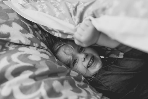silly funny girl hiding under blanket real moment documentary photo