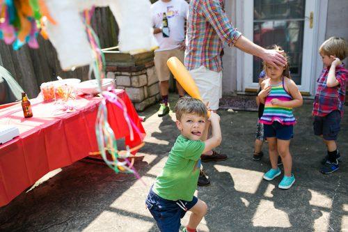silly kid swinging bat at piñata at birthday party