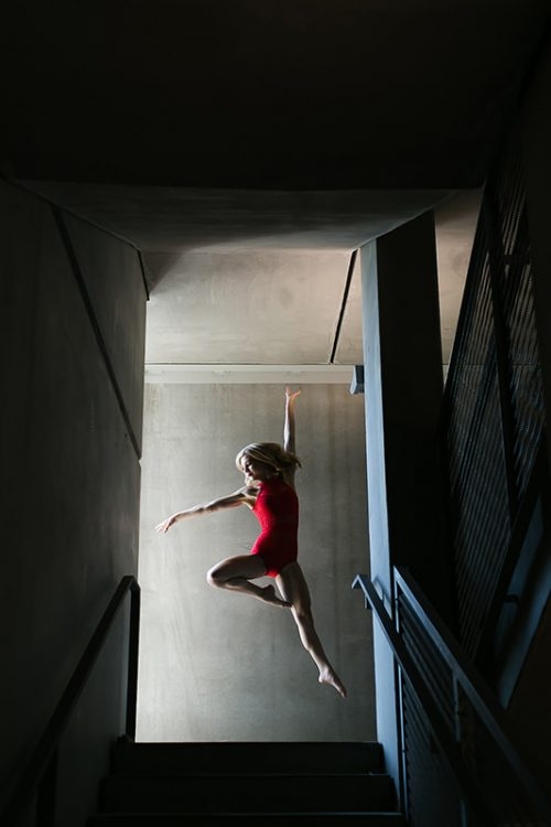 stunning epic jumping dance photo with striking light in stairway for senior pictures