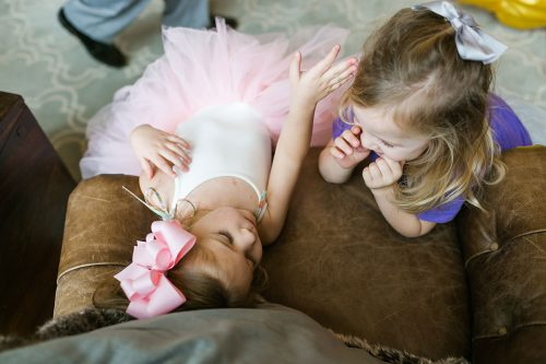 sweet photo of two little girls sharing a ream moment at birthday party documentary moment