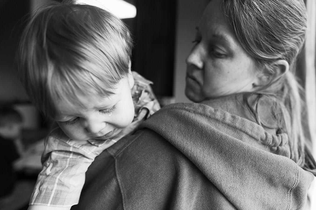 sweet real genuine moment mom holding boy with big crocodile tear Kansas City storytellers