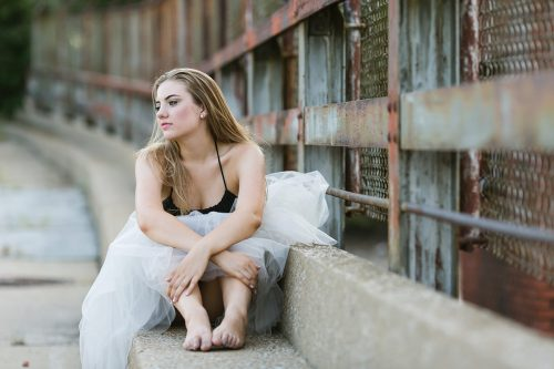 unique stunning dramatic dancer sitting on rusty bridge