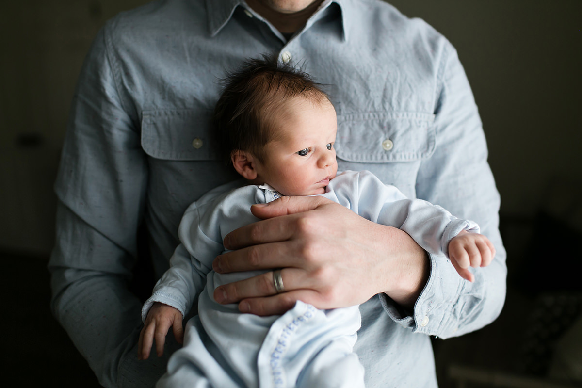 KC newborn photographer sweet baby being held by dad in calm relaxed photo