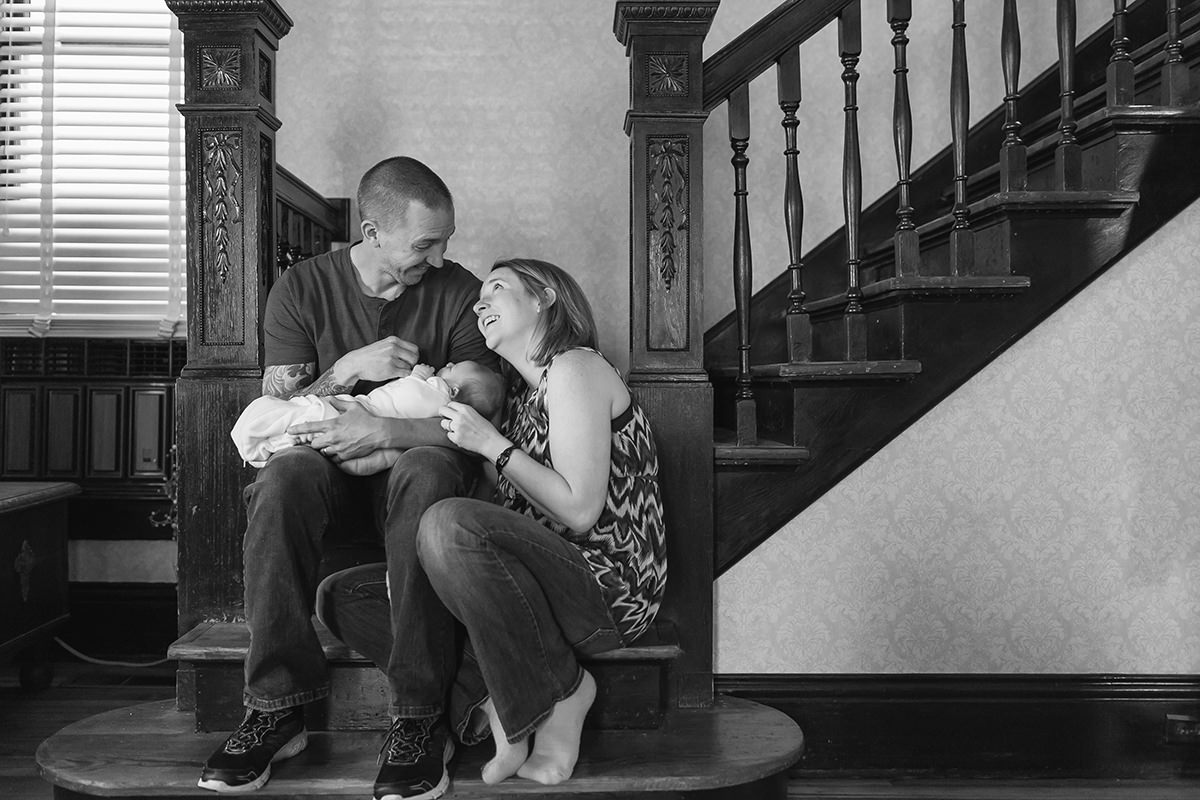 authentic joyful family holding newborn on stairs in-home session