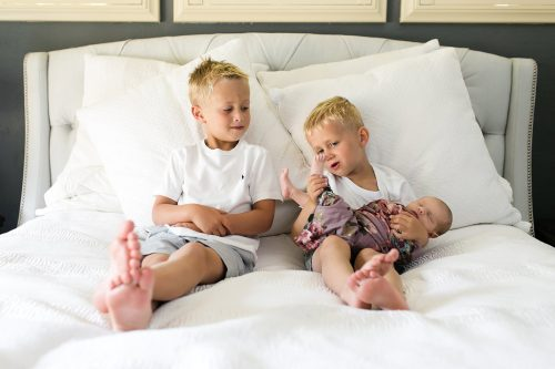 funny cute moment of brothers looking at new baby's feet