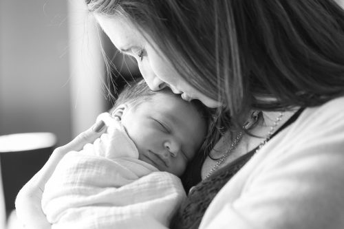 tender genuine loving moment with mother and newborn baby