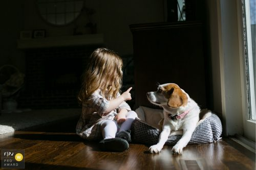 girl talking to dog with finger real life unposed photo family photojournalist award