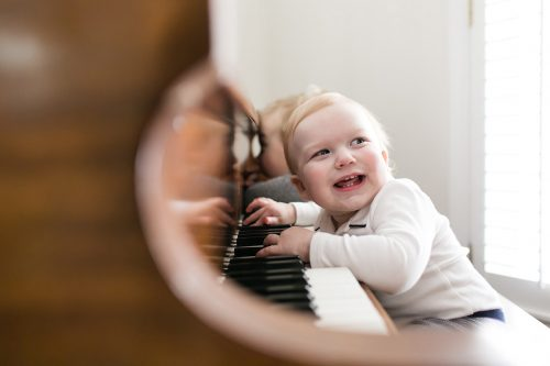authentic in-home family photo sessions kid playing on piano picture