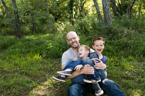 dad roughhousing with two laughing kids in woods family photo session picture