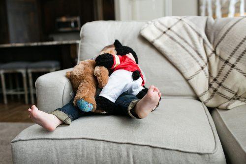 fun Kansas City family photographer kid covered in stuffed animals photo