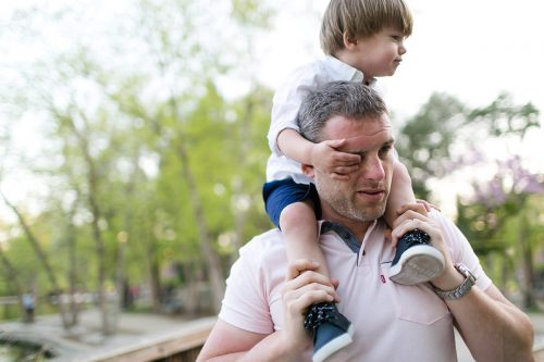 fun pic of kid grabbing dads face during relaxed family picture session